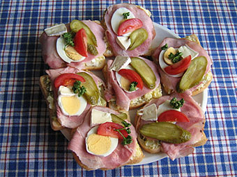 Classic ham : butter bread slice, top with spoon of potato salad, salami or ham, slices of egg, pickle, tomato and parsley.