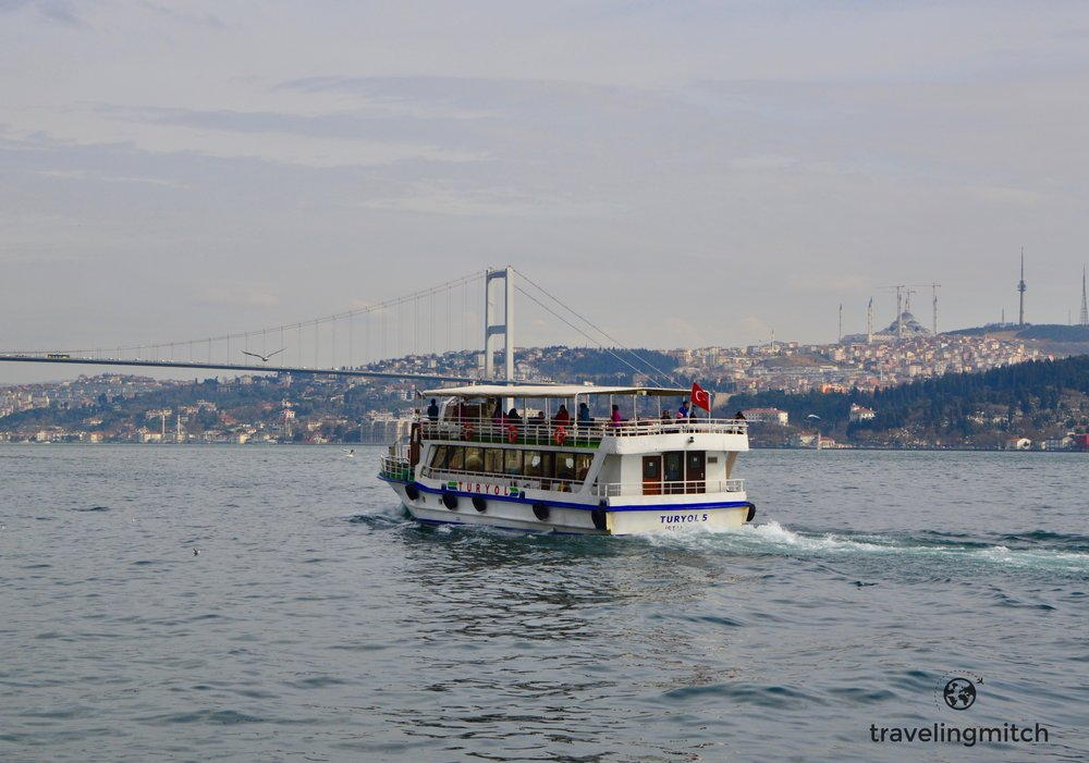 A tourist boat politely chugs along the Bosphorus near Örtaköy, Istanbul, Turkey