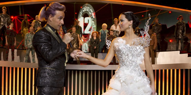 Stanley Tucci as Caesar Flickerman, who hosts the  Hunger Games broadcast