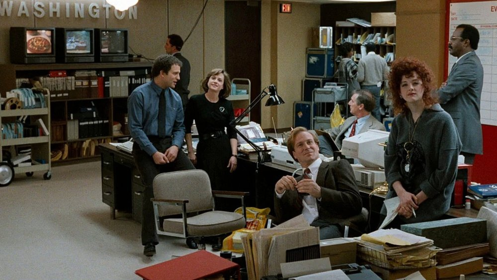 Jane and Aaron work at the Washington station of a major network with Tom Grunick (William Hurt, centre).