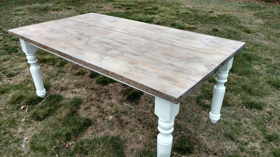 Farmhouse table with turned legs and stained top with a grey finish