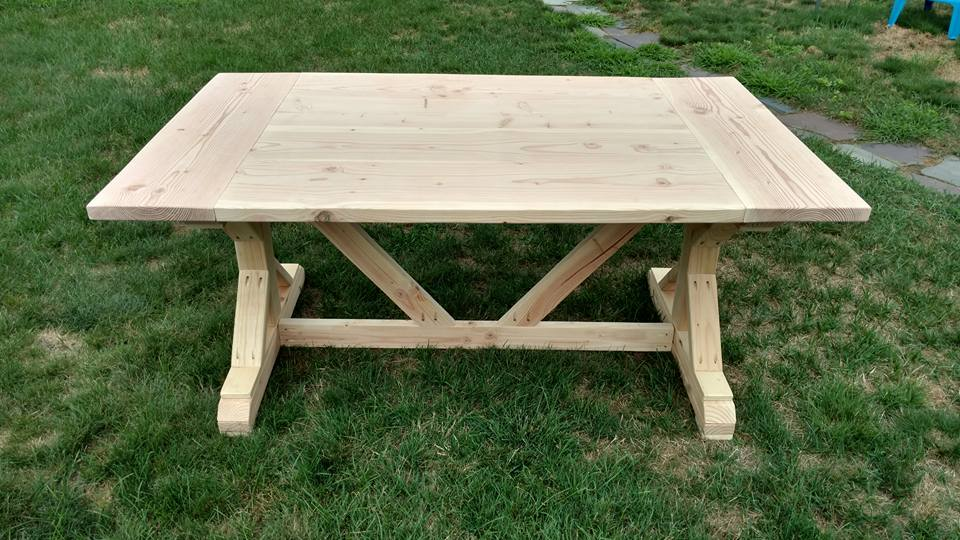 Unfinished trestle style table with bread board ends