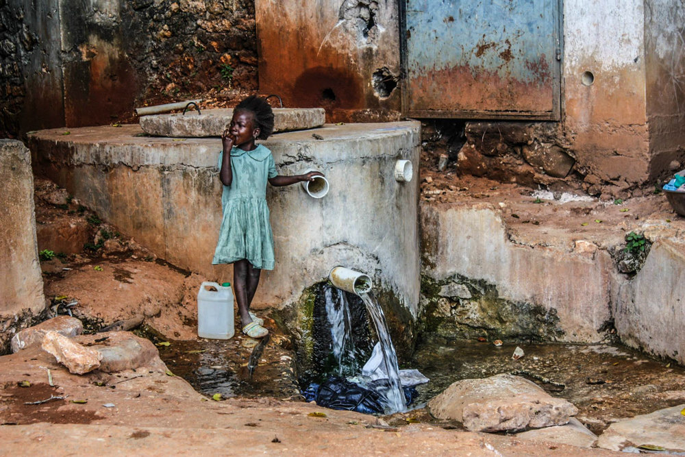 A young girl stops to collect water for her family at one of the only clean water sources in the village and surrounding areas of La Vallée. More than forty percent of the Haitian population lacks access to clean water on a daily basis.