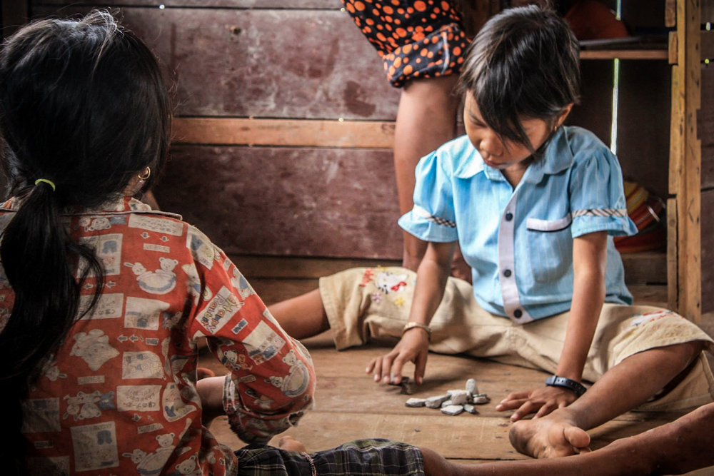 Students at a volunteer-run school play a game with rocks during a moment of calm during the schoolday.