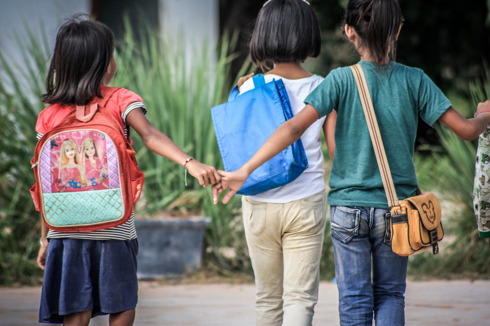 A group of girls walk to class together.