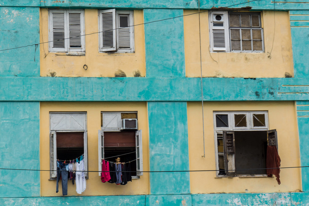 A woman hangs clothes to dry from her apartment in Havana.