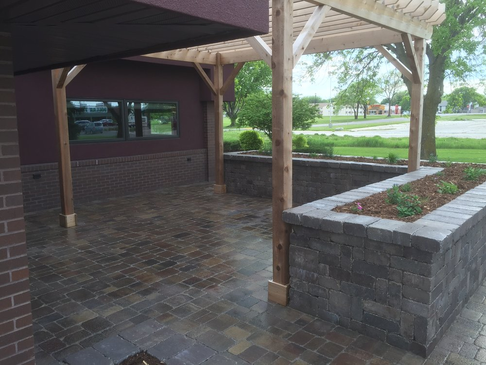 A beautiful patio, planter beds, and a pergola.