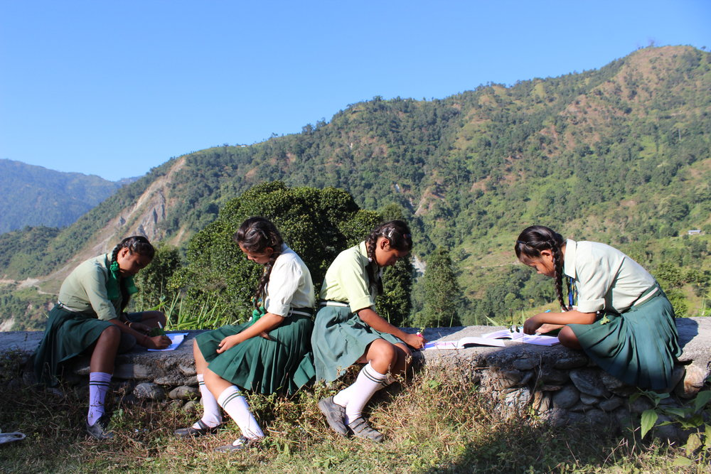 Local Chuikhim school girls drawing in front of a scenic view...