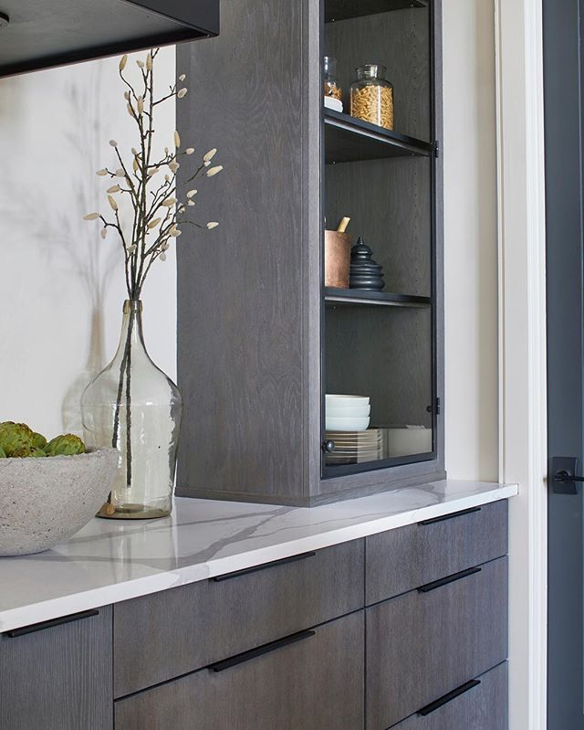 Cerused oak by our favorite cabinet maker for the @atlantamagazine @pinewoodforest Idea Home. We wanted the patina but didn't want to do the expected white oak/white finish. So we came up with a mix of warm dark gray that nods to the current trend but will stand the test of time. We designed glass and iron doors for the two towers to keep it clean and modern and speak to the iron band we used on the plaster hood. We're calling this mash up DLD meets @gameofthrones - we went just a touch castle on this one.