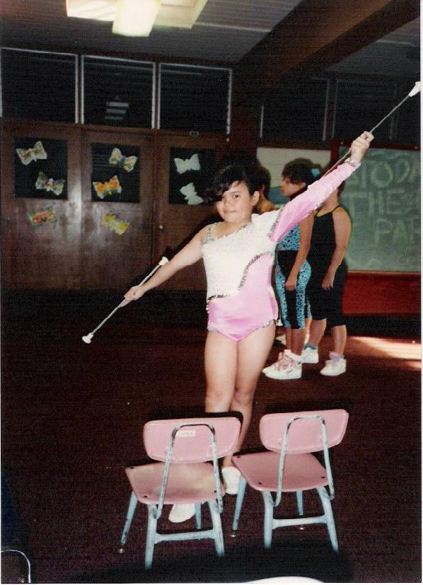 8-year-old Kristl proudly posing after a baton performance.