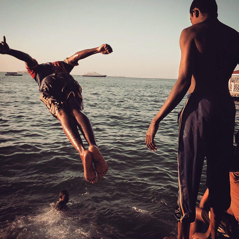 Teens dive into the ocean at sunset  Stone Town, Zanzibar