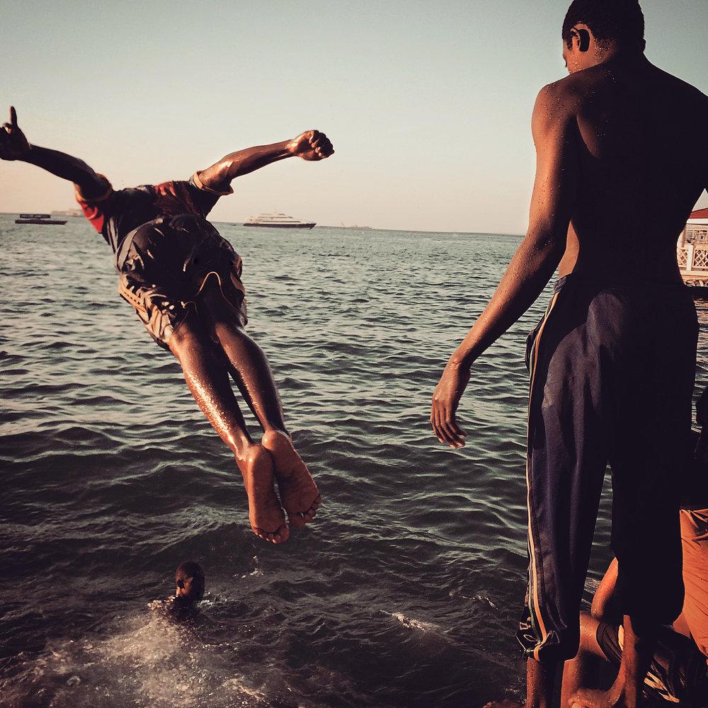 Teens dive into the ocean at sunset  Stone Town, Zanzibar