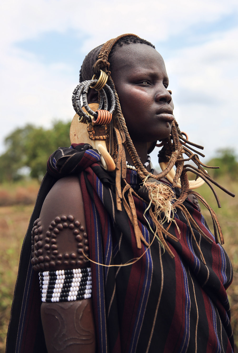 The sign of beauty among Mursi women are large lip plates and scarification, sported by almost all of the adult women. When a Mun (as they call themselves) becomes engaged to be married, usually around 14 or 15, she disappears from village life to live in her family hut. The gap between her front lip and the flesh below is pierced and gradually stretched. In the beginning a hole is made in the lip with a wooden stick. The stretching continues as successively bigger discs of clay or wood are accommodated by the changed lip. Generally the two lower front teeth are pulled or knocked out to aid in the process. The final size of the plate helps to determine her beauty & bride price.