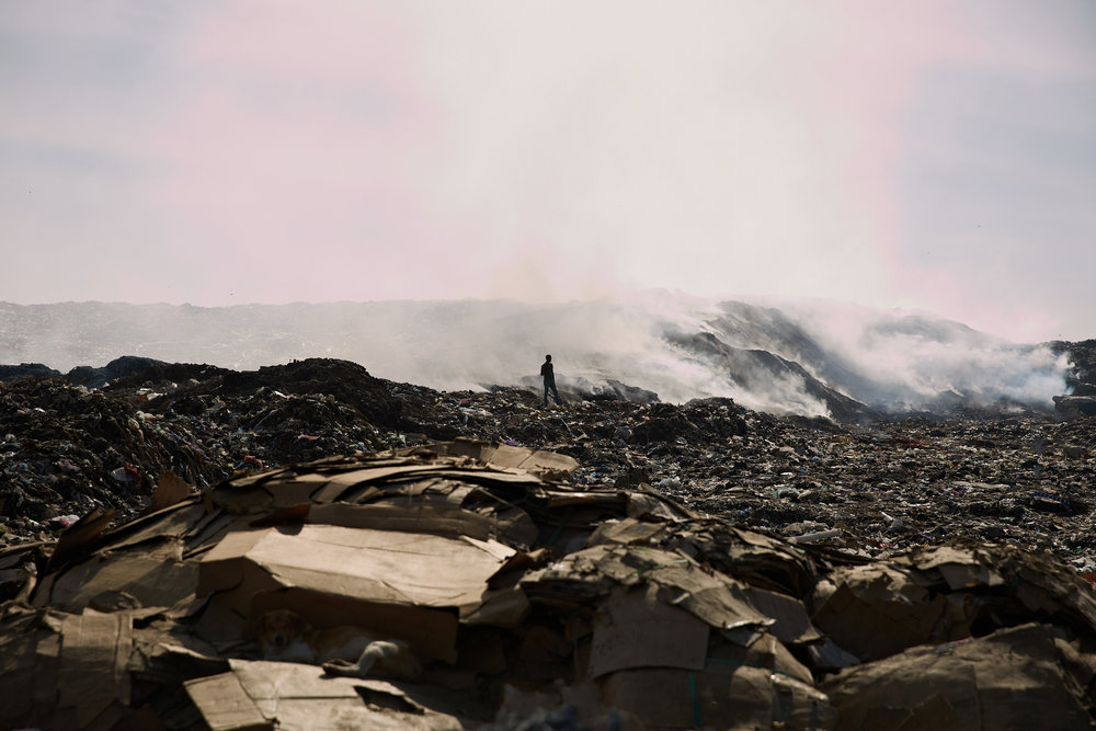 In landfills that don't cover their waste,biological decomposition creates substantial heat which causes material in the landfills to spontaneously combust. There are constant plumes of smoke which make breathing difficult for  its residents   Addis Ababa, Ethiopia
