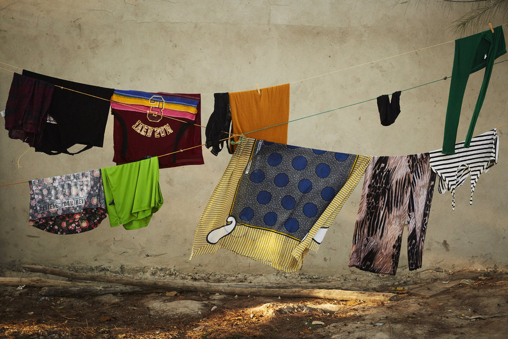 The women live & work at the bar. During the day they handwash their laundry and hang to dry on a line