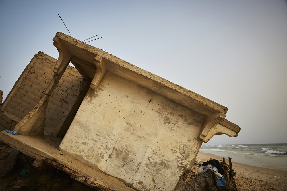 A portion of a house breaks off onto the sand in Saint-Louis, Senegal.  Homes on the waterfront have been destroyed by the rising tide.
