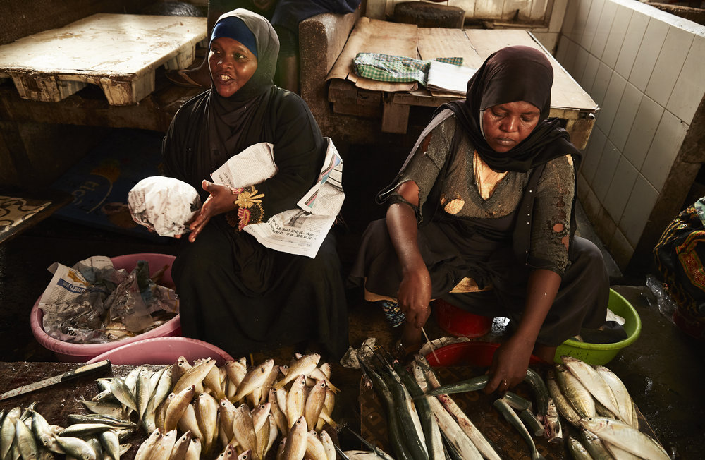 Women clean fish to sell at the local market  Stone Town, Zanzibar