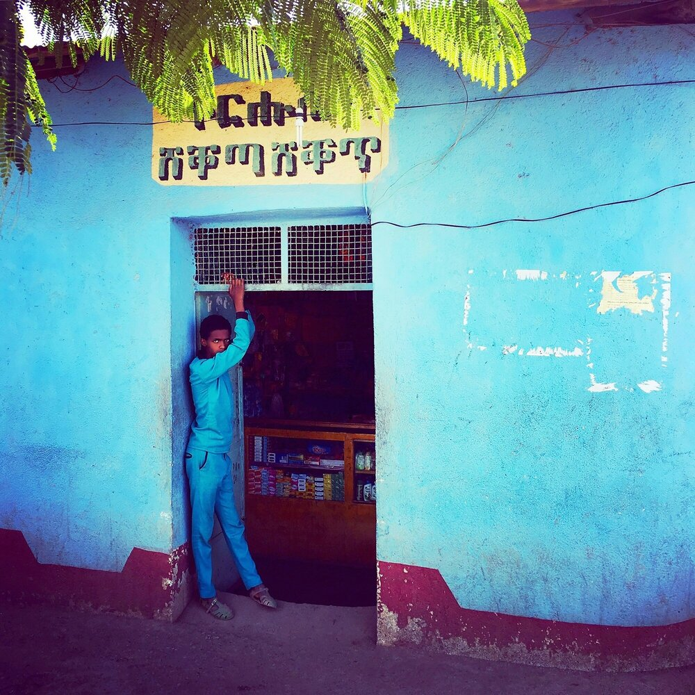 Teen waits for customers outside his family's shop  Shire, Ethiopia