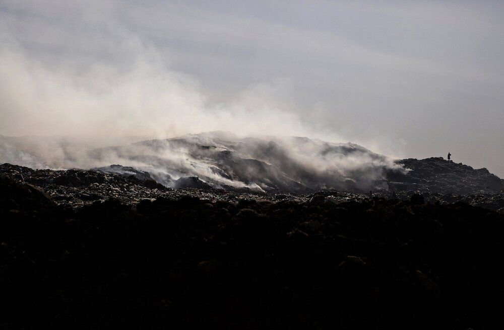 In landfills that do not cover their waste, biological decomposition creates substantial heat causing the materials to spontaneously combust.     The constant plumes of smoke make breathing difficult, for the roughly 300 people who work & live here.