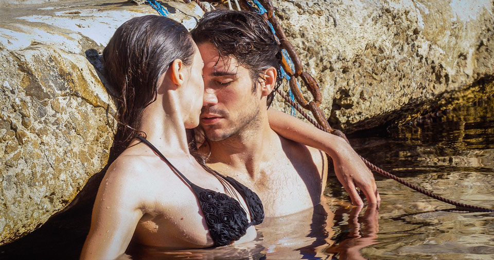 "PHOTO:  Carmen & Giovanni cool off in the Blue Grotto.  (L to R) Marysia S. Peres and Myko Olivier star in "" LOVE TO PARADISE "". Photo: Courtesy of Galea Pictures. © 2017 Galea Pictures. All Rights Reserved."