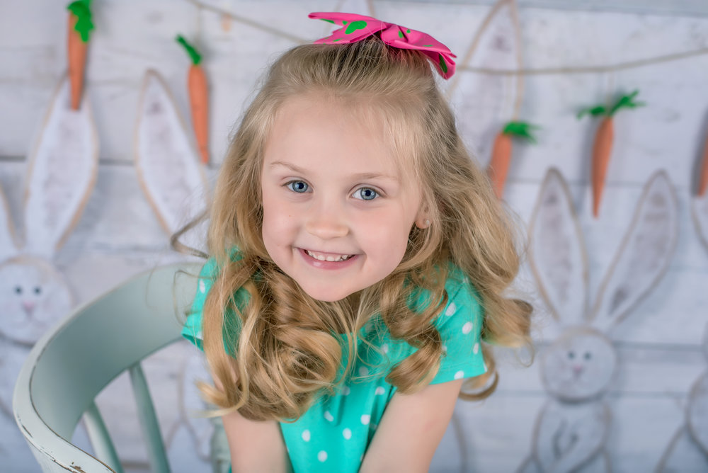 Little blond girl in green at easter portraits with bunny and carrots