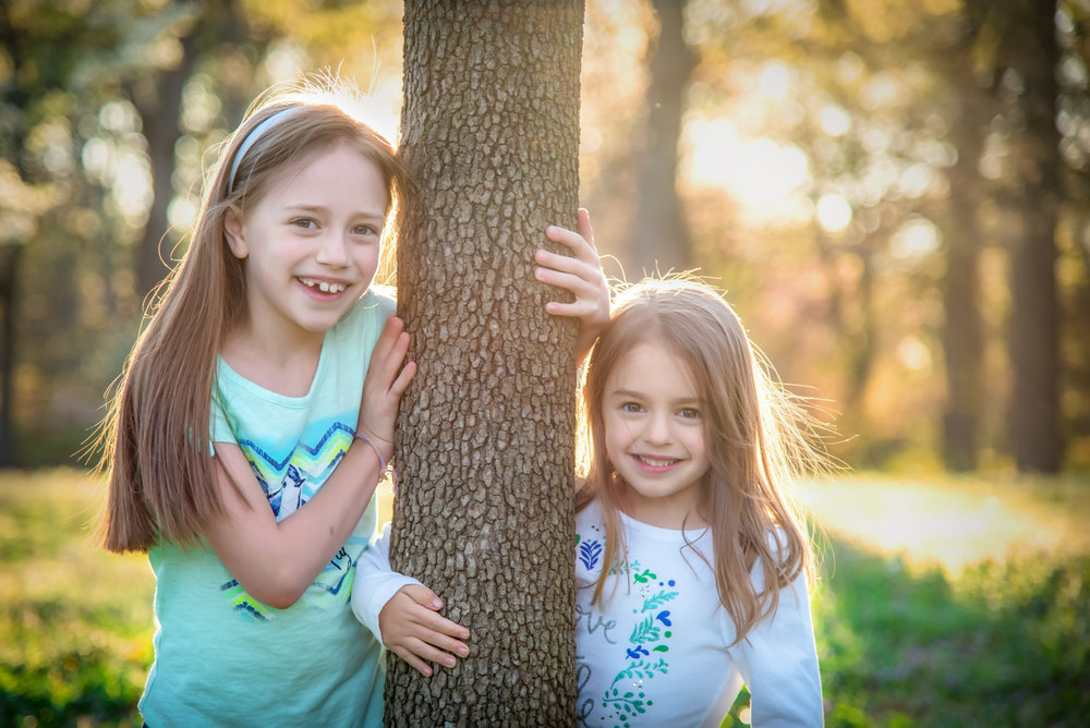 Sisters hugging around tree in Bryan Park in Richmond Virginia