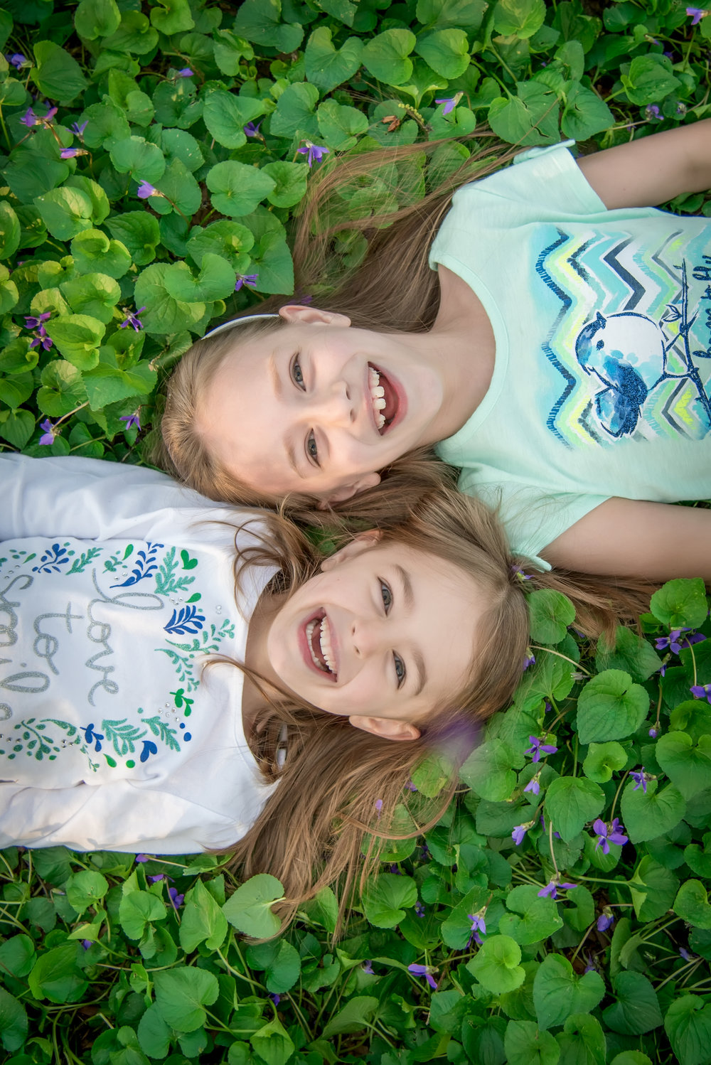 Sisters laying in a field of clovers at Bryan Park in Richmond Virgnia for Spring Family Portraits