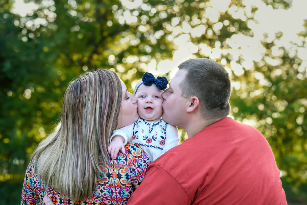 Family of three kiss in Hopewell Viriginia at fall family portrait session