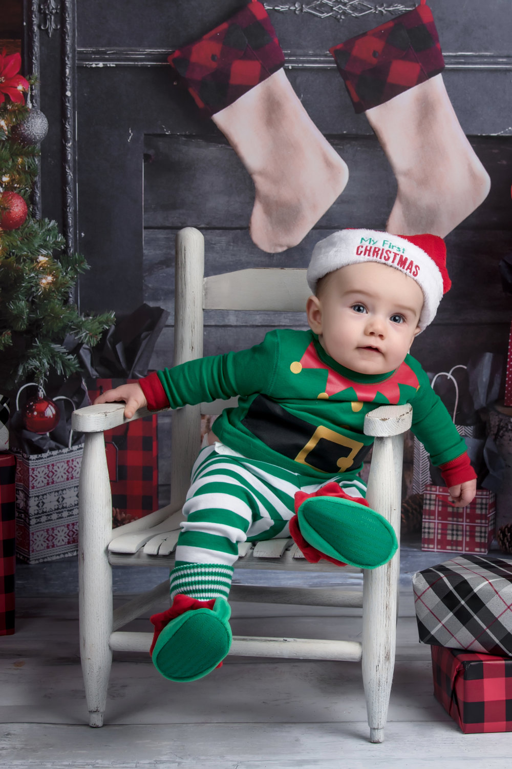 Little boy elf Christmas holiday mini session with stockings and mantel
