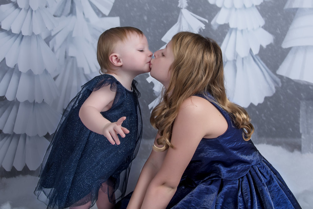 Sisters kissing in Blue winter scene holiday christmas mini session