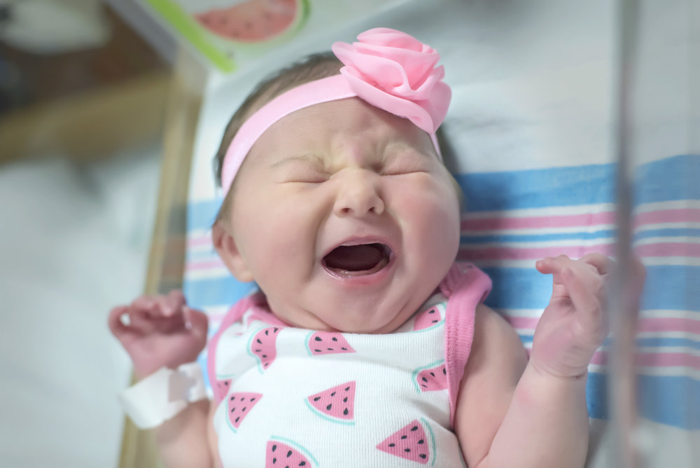 Crying newborn baby girl at fresh 48 photography session