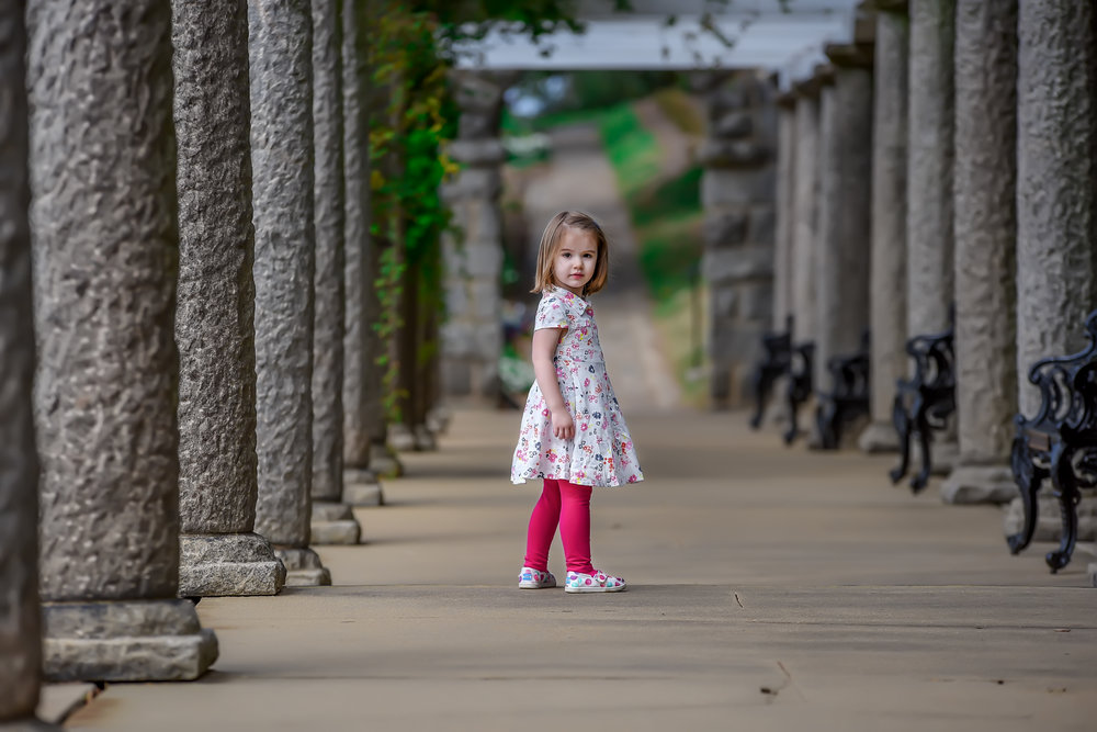 Little girl between rows of columns at maymont in Richmond Virginia