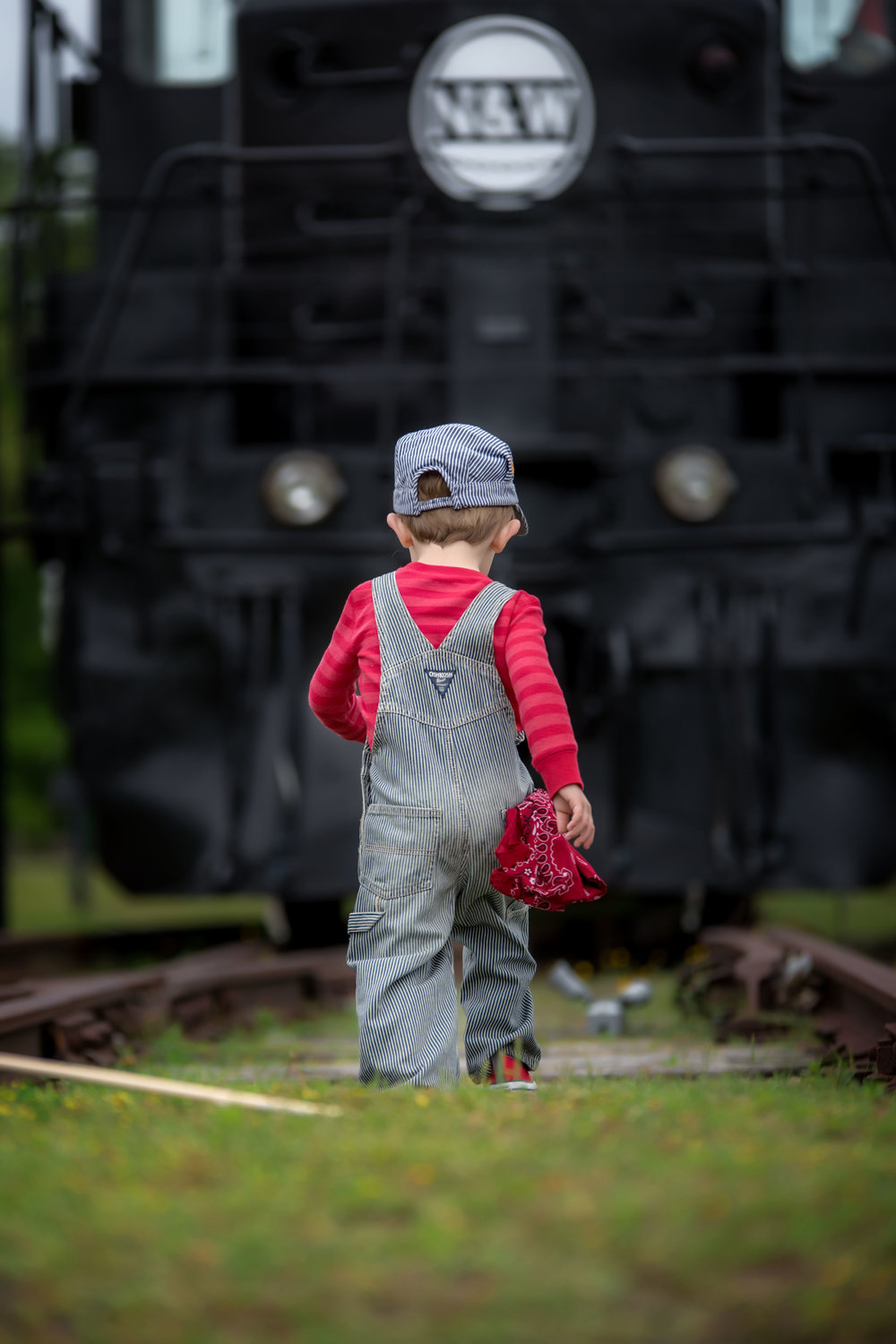 3 year old little boy in train conductor engineer outfit at Rail Road museum in Crewe Virginia