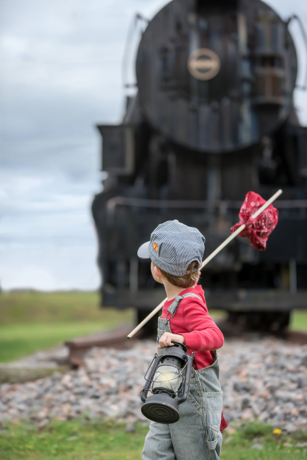 3 year old little boy in train conductor engineer outfit with lantern and hobo stick