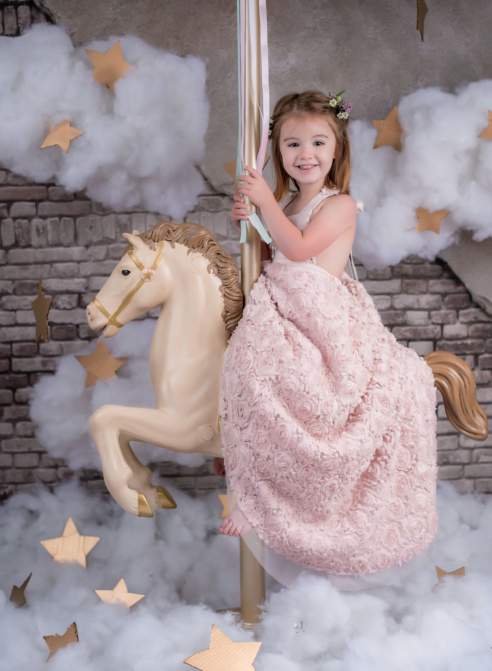 3 year old Little girl in pink rose princess dress on Carousel horse with brick background and clouds, fantasy magical setting