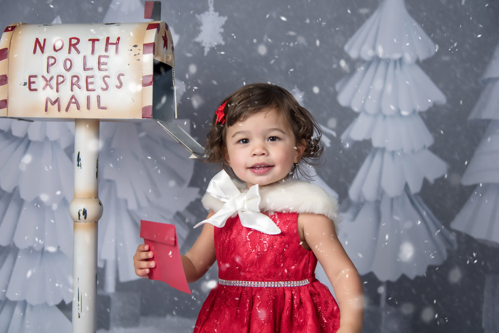 North Pole Express Mail snow holiday christmas mini session with little girl in red dress