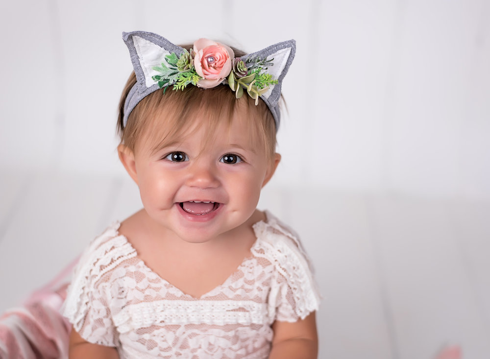 1st birthday portrait of baby girl in cat ears wearing pink and gray