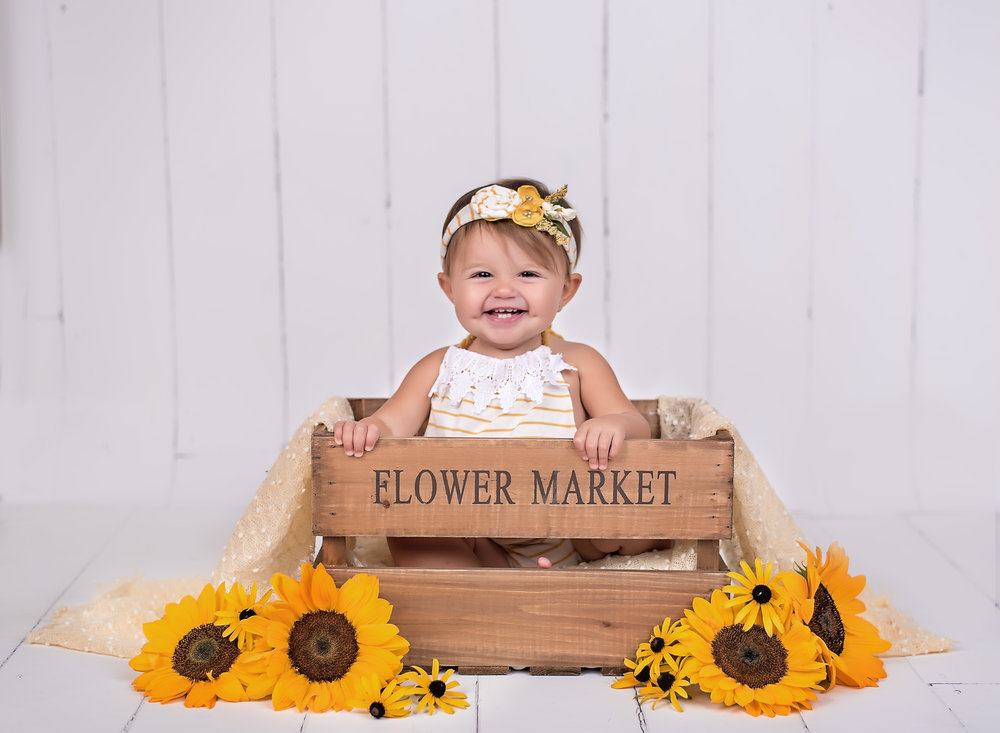 Little girl in flower market box with sunflowers