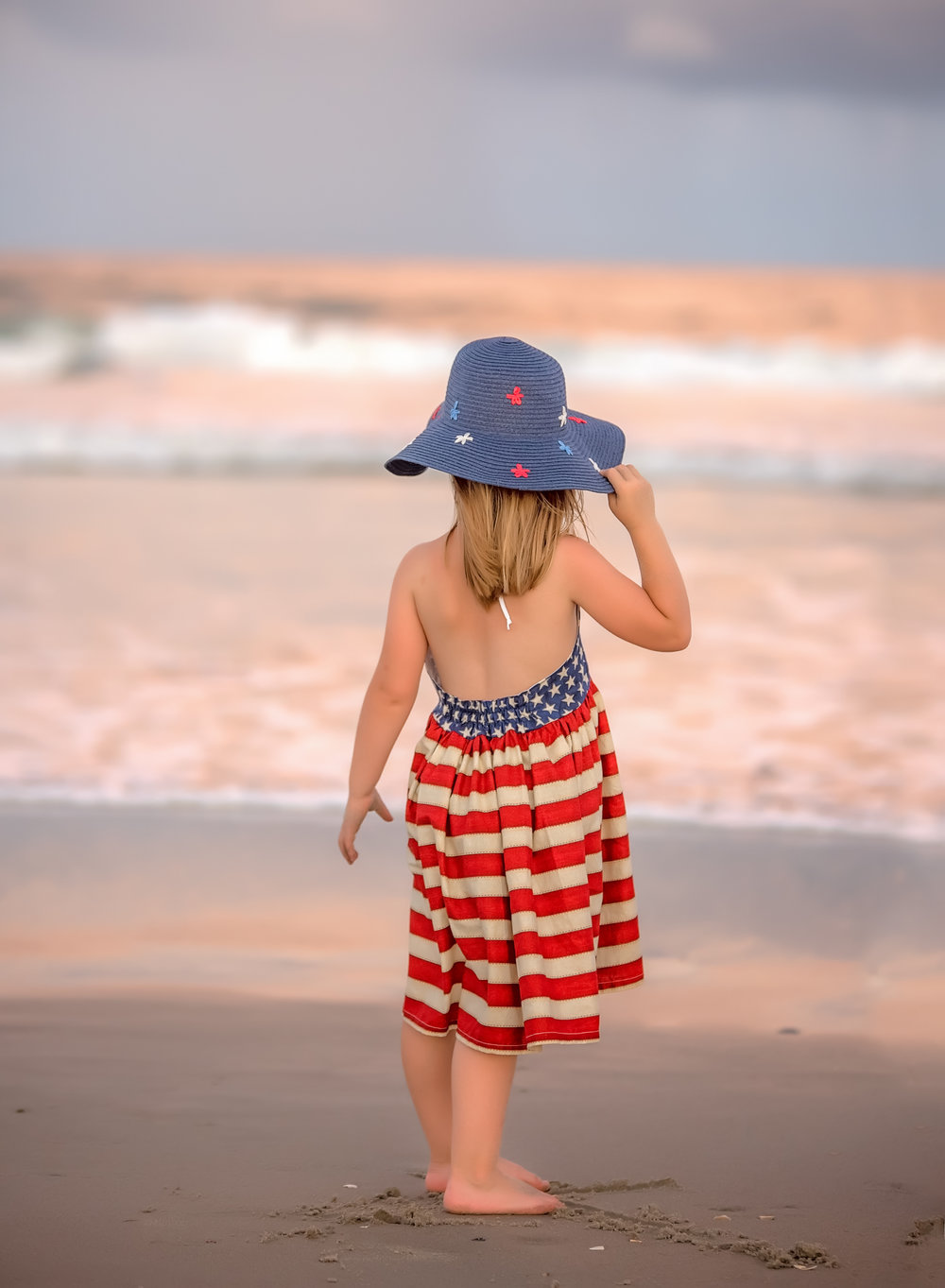 patriotic red white blue flag little girl at ocean on fourth of july at ocracoke island north caroline at sunset