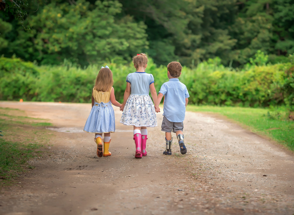 children in blue and yellow holding hands walking down dirt road country lane