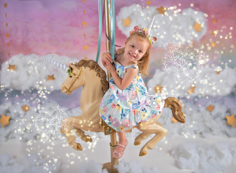 little girl on Unicorn in studio mini session with giltter