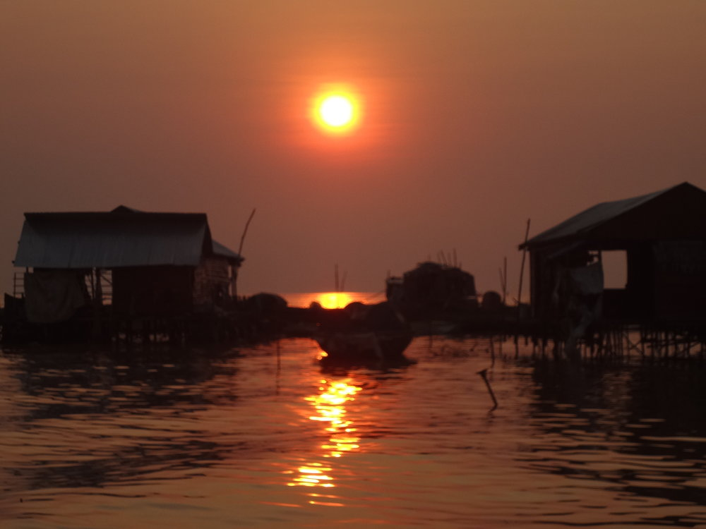 """The sun was setting and it was time for us to head back up river. On the way we saw fishermen and women hauling in the day's catch. We also saw boatloadsl of large white sacks full of snails that were taken from the lake that day. The snails will be washed and seasoned and left on carts in the sun to """"cook"""" and sold on the streets of Siem Reap and nearby villages as lunch. I asked Chamnan if he eats them. He does, but warned us not to because they would make us sick. Seeing the muddy water and knowing that human waste goes directly into the lake here, I don't think we'd be tempted to try the snails anyway."""