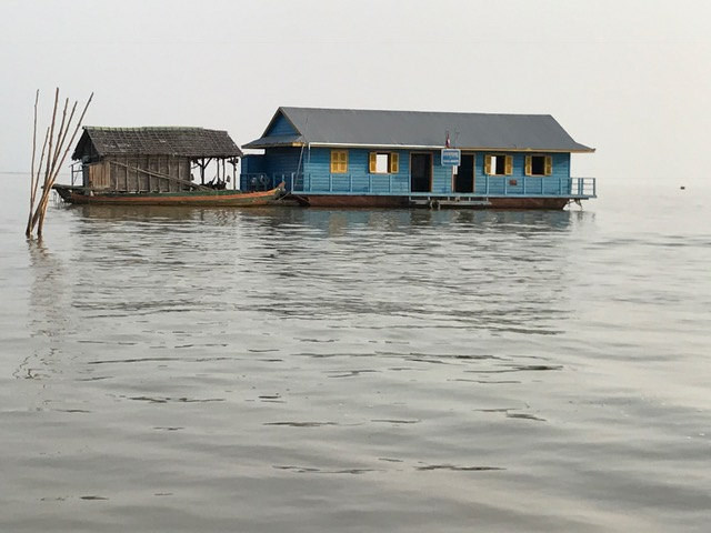 "This is the school for the floating village. Chamnan estimated that about 60 children attend here. All grade levels. One teacher. There's no ""bus"" or boat that picks the kids up and takes them home. The water level is so low that they are able to tie the school to the sticks on the left to hold it in place for now."