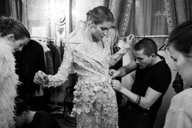 Timo adding fresh flowers to a dress backstage at a  Eva Poleschinski  fashion show.