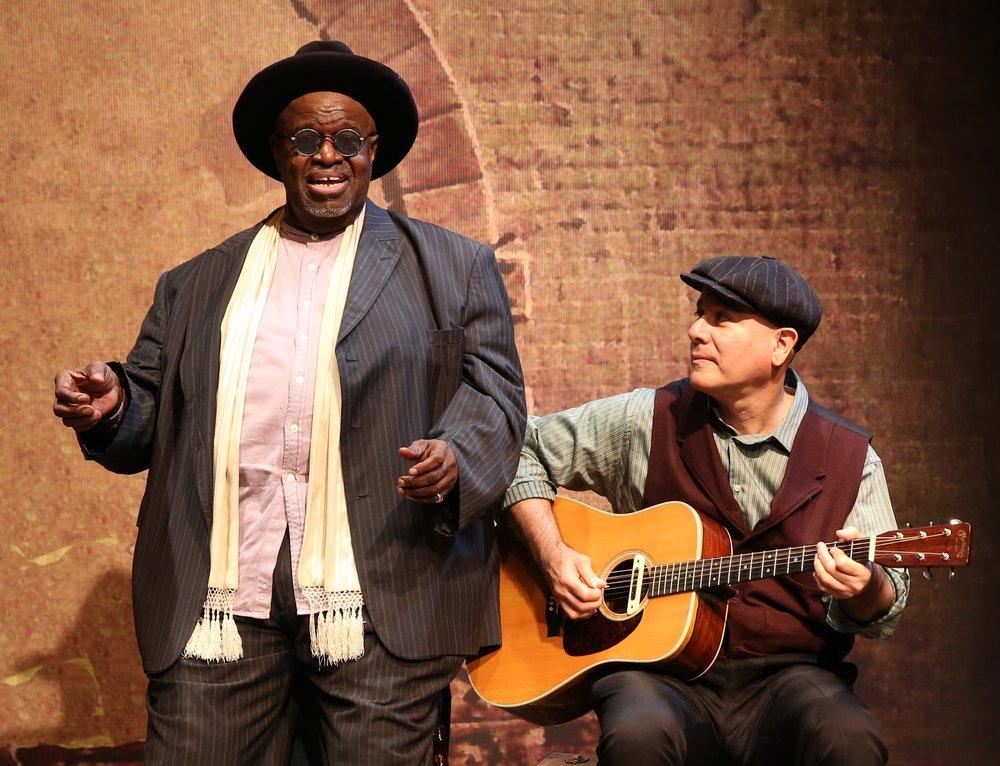 Akiń Babatundé (left) as the prolific, itinerant Texas bluesman Blind Lemon Jefferson, with David Weiss on guitar. Top: Babatundé as Jefferson. Photographs by Carol Rosegg.
