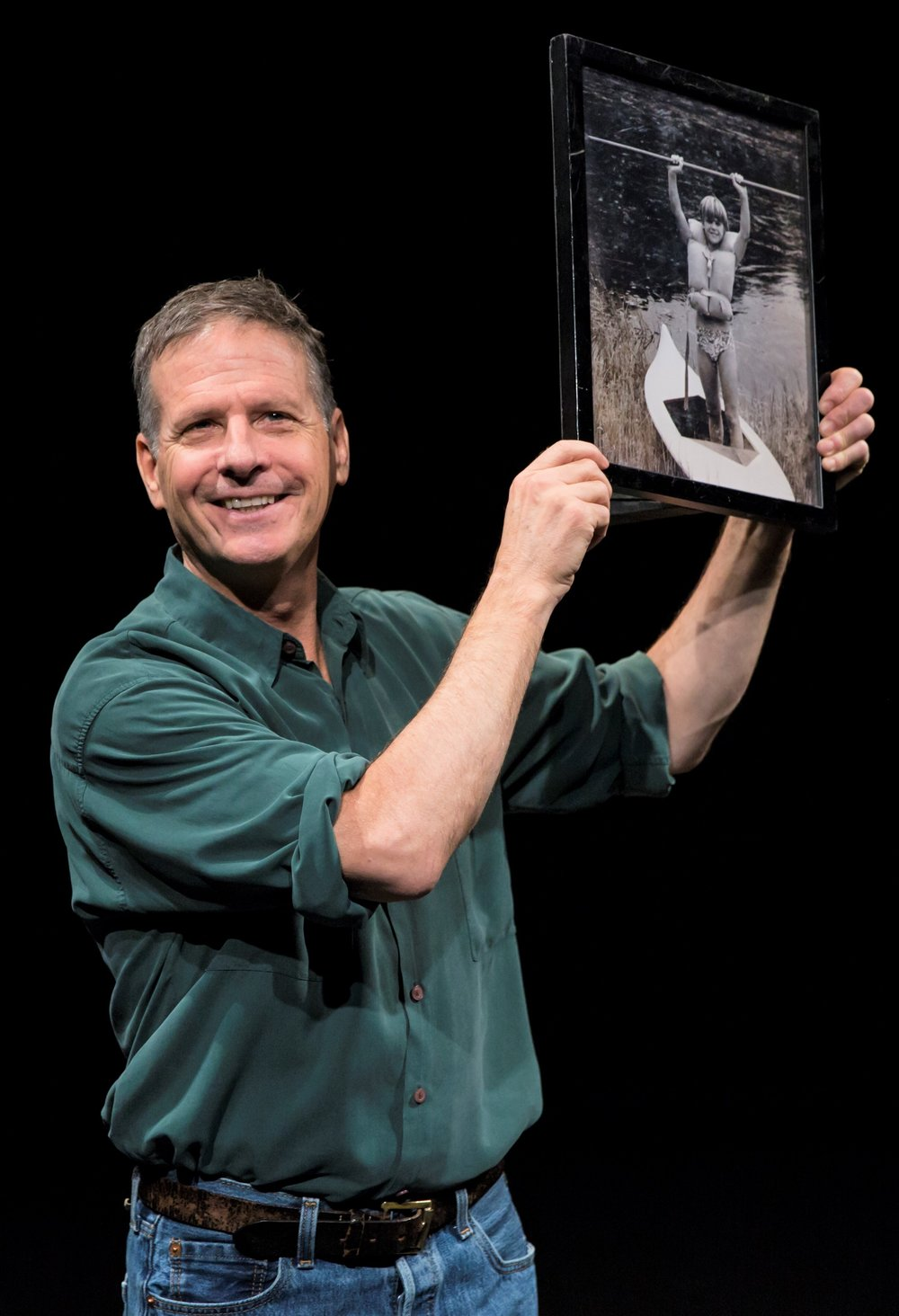 Martin Moran displays a photograph of himself at age 12 that was taken by camp counselor Bob. Top: Moran addresses the audience in the Barrow Group revival of  The Tricky Part .