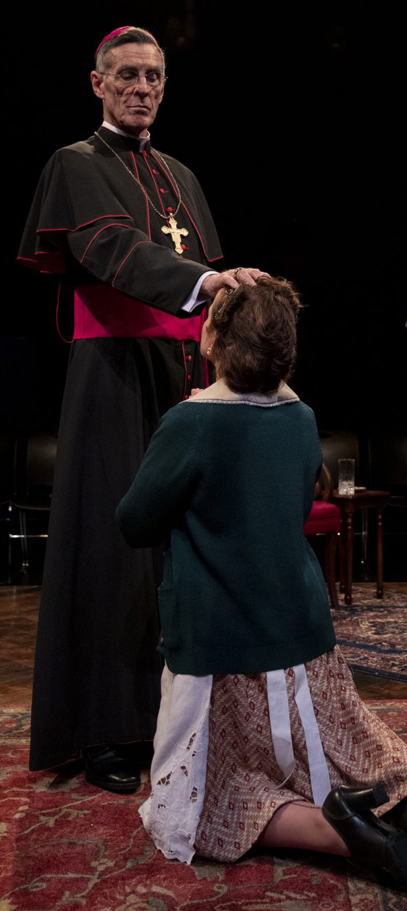 Bishop von Galen (John Glover) blesses Martha (Jennifer Dundas), in Stephen Unwin's  All Our Children . Top: John Glover (left) as Bishop von Galen, Karl Kenzler (center) as Victor Franz, and Sam Lilja as Eric Schmidt.