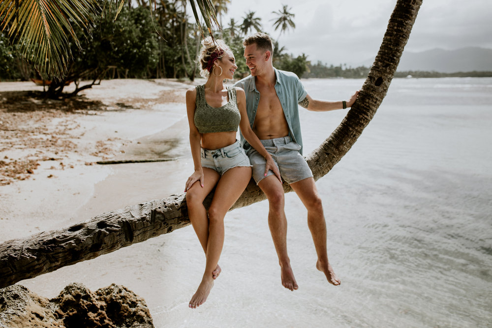 couple sitting on a tree on an island