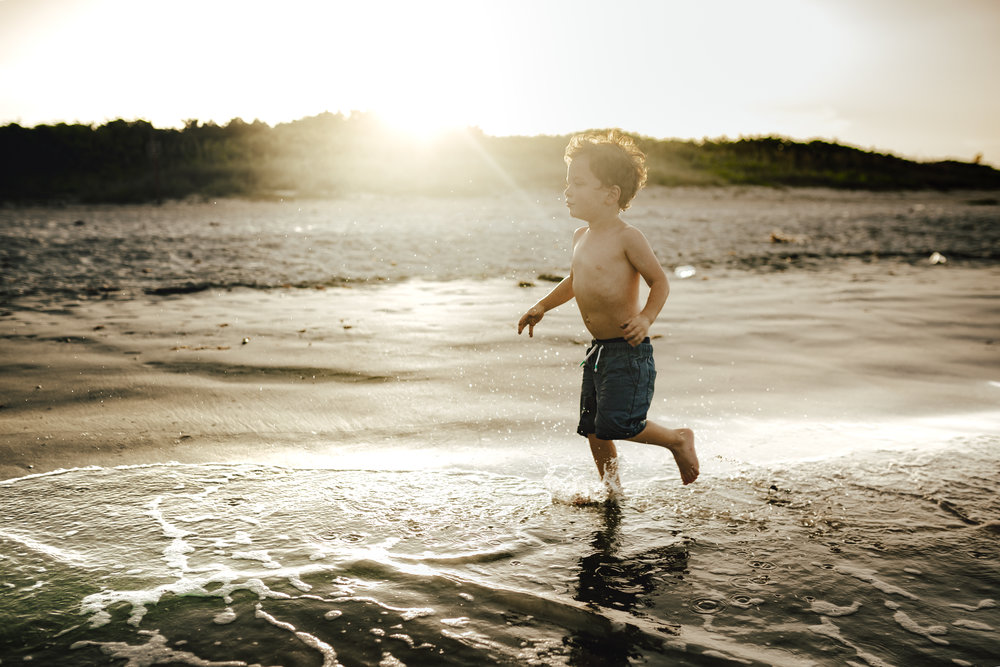 boy running through the ocean at sunset