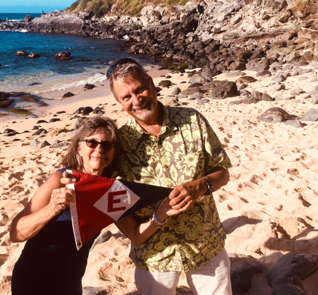 Mark & Sheena Schroeder sport the EYC burgee on a beach in Maui—they note that the 'rocks' behind them are actually sea turtles coming ashore.